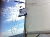 Die ARC-Flagge vor dem Großsegel der Luv, darüber der clubstander der SVAOe.